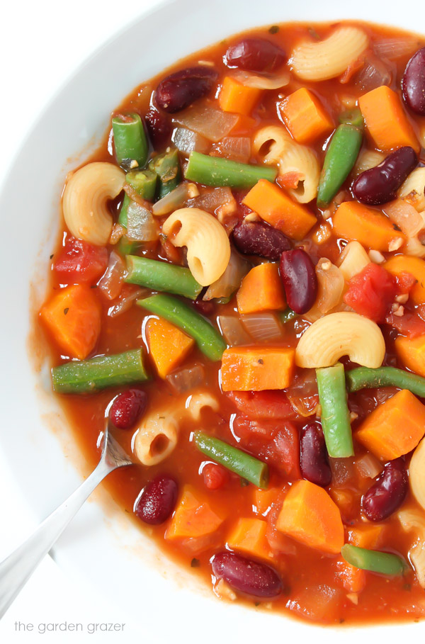 Close up view of minestrone soup in a bowl with spoon