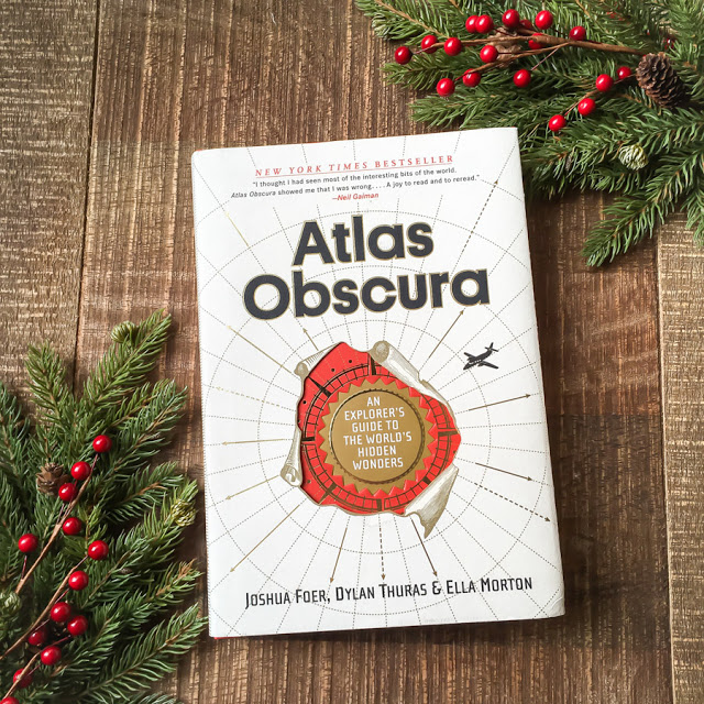 Atlas Obscura book on a wooden table
