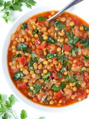 Bowl of vegan Lentil Tomato Soup with spoon
