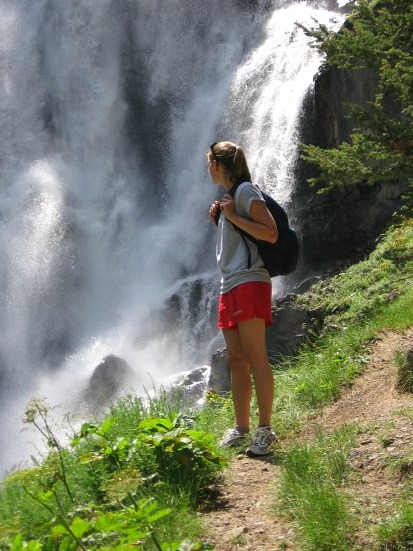 Kaitlin on a hiking trail in Yellowstone near a waterfall
