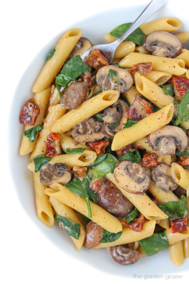 Creamy vegan pasta with mushrooms and sun-dried tomatoes on a plate