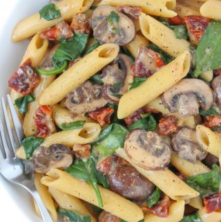 Creamy sun-dried tomato mushroom pasta in a bowl with fork