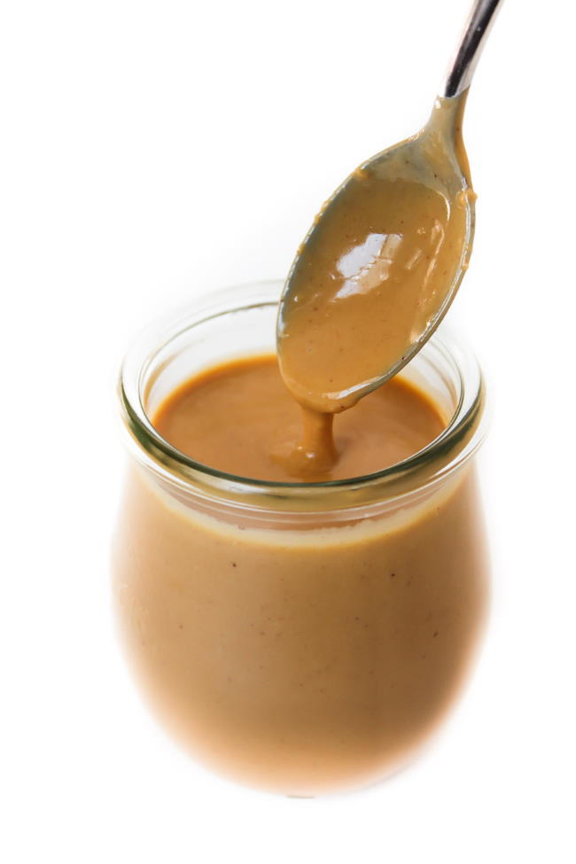 Small glass jar filled with creamy Thai Peanut Sauce and a spoon