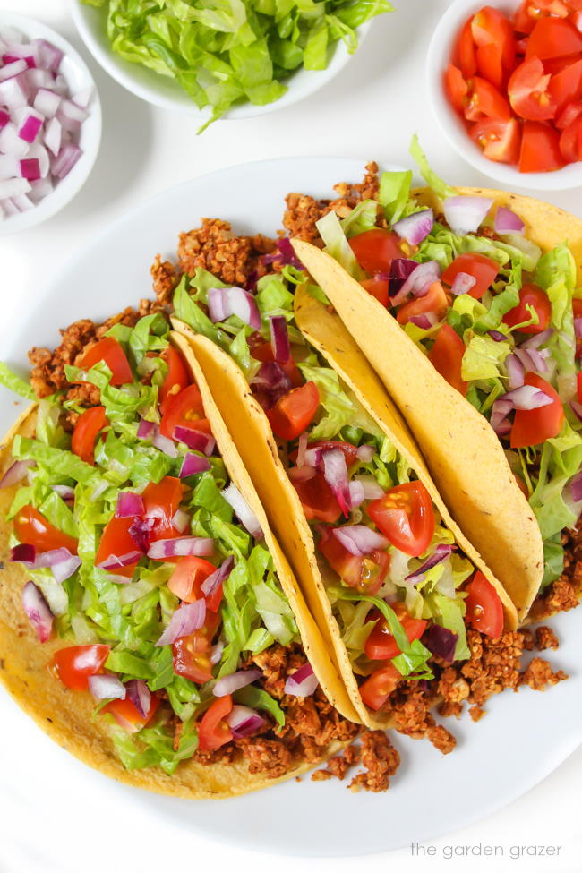 Plate of chickpea walnut tacos with lettuce, tomato, and onion