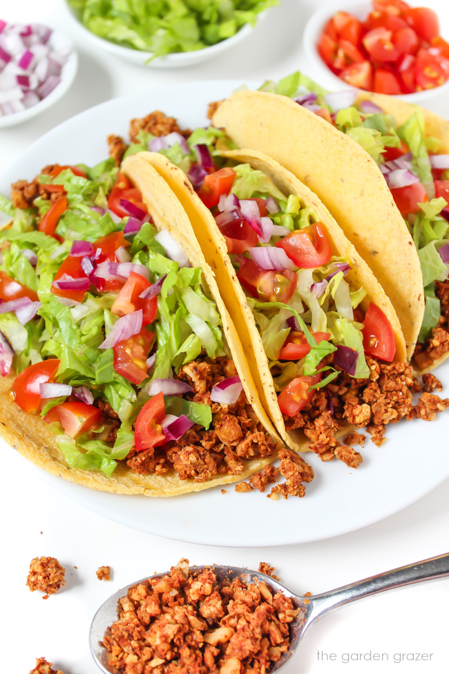 Plate of three vegan tacos with chickpea-walnut taco filling