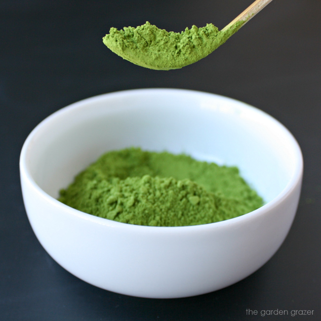 Bamboo scoop holding ground organic matcha