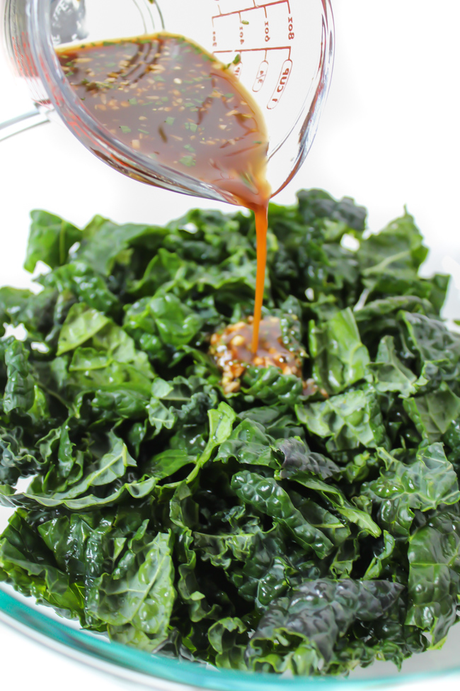 rosemary maple balsamic dressing being poured over chopped kale