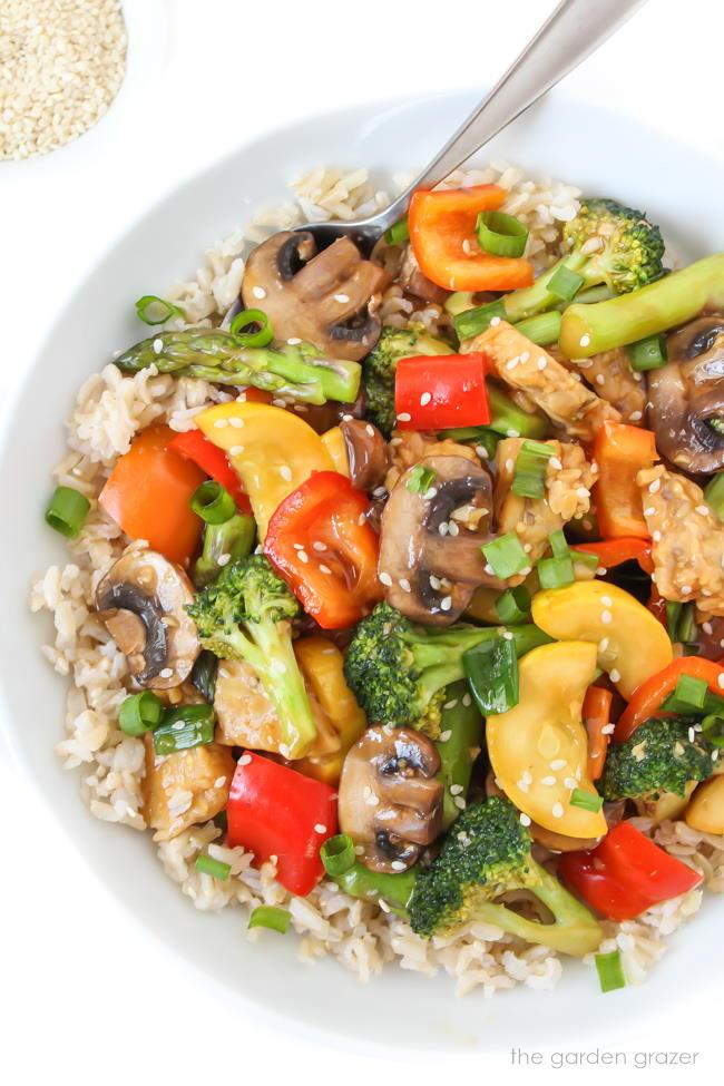Bowl of vegan teriyaki vegetable stir fry garnished with sesame seeds