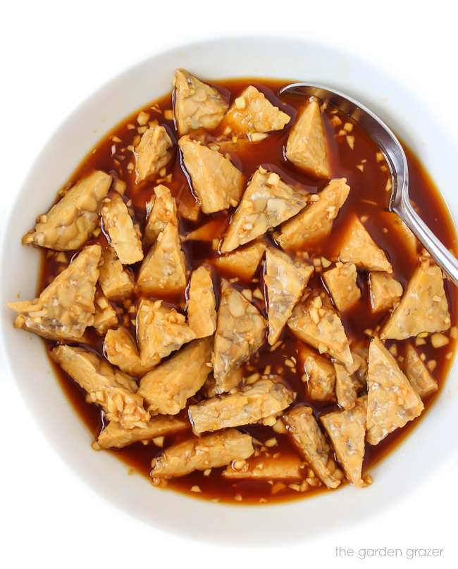 Triangles of tempeh marinating in teriyaki sauce in a bowl