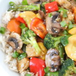 Vegetable tempeh teriyaki stir fry in a bowl with brown rice