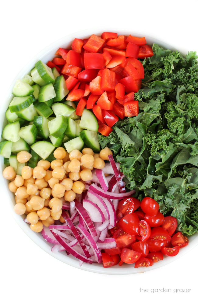 Ingredients for Kale Greek Salad in a large bowl