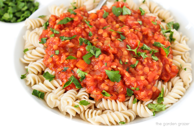 Vegan red lentil bolognese over pasta in a bowl with fresh parsley