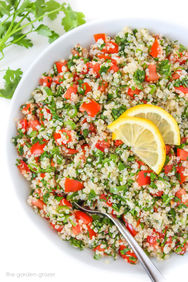 Vegan quinoa tabbouleh in a bowl with lemon slices