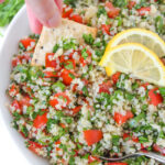 Cracker dipping into bowl of quinoa tabbouleh salad