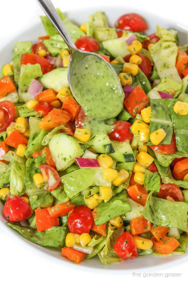 Vegan summer chopped salad tossed with herb dressing on a plate with spoon
