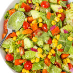 Bowl of summer salad tossed in creamy avocado dressing with spoon