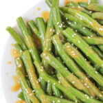 Vegan miso-glazed green beans on a plate with sesame seeds