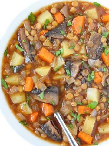 Vegan mushroom potato lentil stew in a bowl with spoon