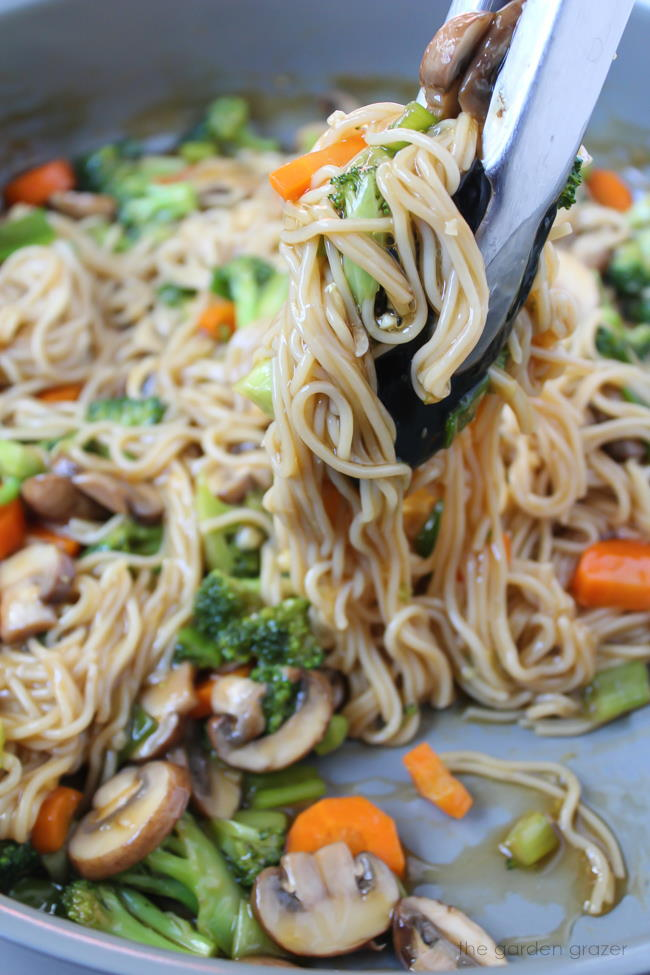 Pan of vegan noodles with teriyaki sauce and vegetables
