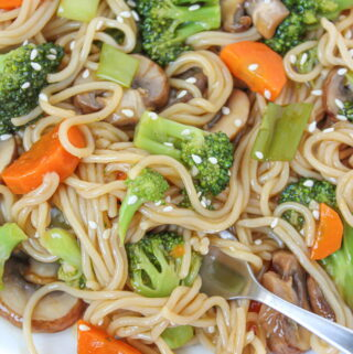 Plate of teriyaki noodles with vegetables topped with sesame seeds