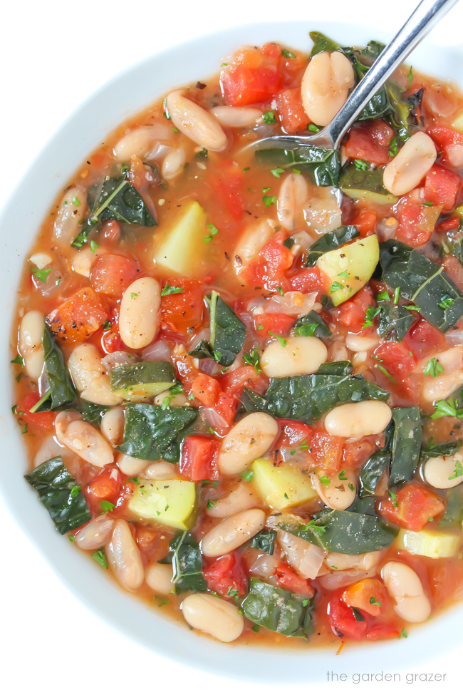 Bowl of vegan fire-roasted tomato and white bean soup with kale