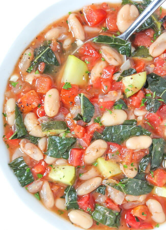 Vegan white bean soup with tomatoes and kale in a bowl with spoon