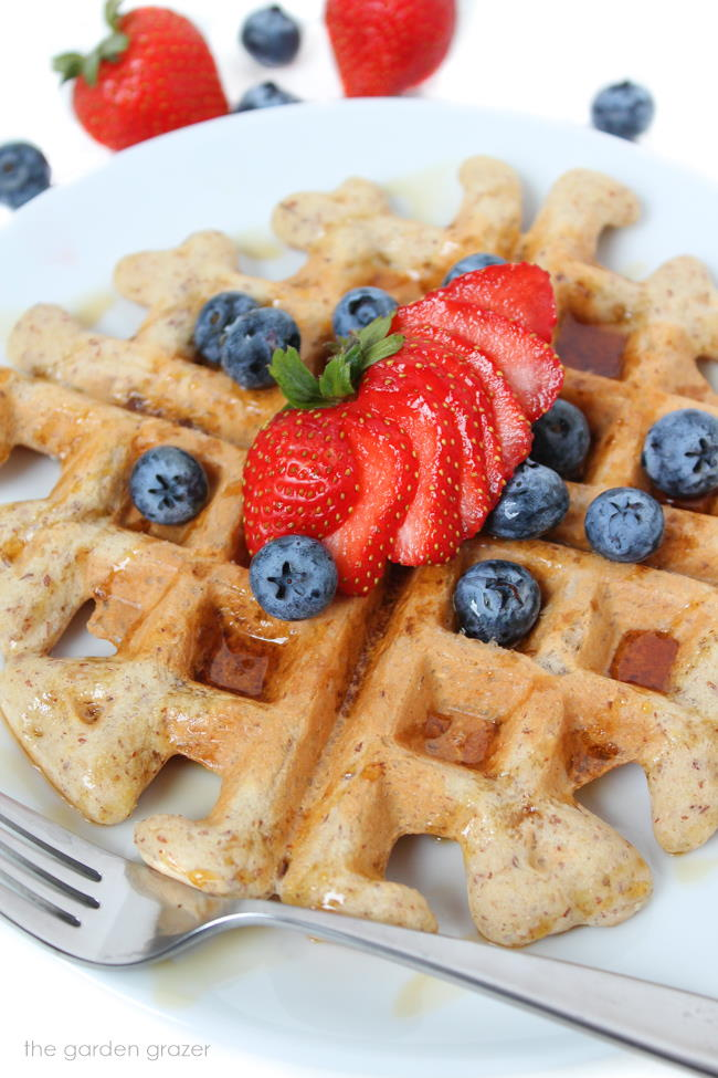 Gluten-free vegan waffle on a plate with strawberries and blueberries