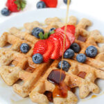 Plate of vegan gluten-free waffles with maple syrup