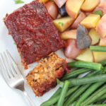Vegan gluten-free meatloaf on a plate with green beans and potatoes