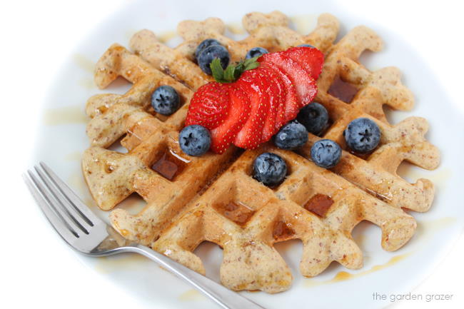 Vegan gluten-free waffle on a white plate with fresh fruit and fork