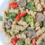 Plate of vegan creamy garlic pasta with broccoli and mushroom