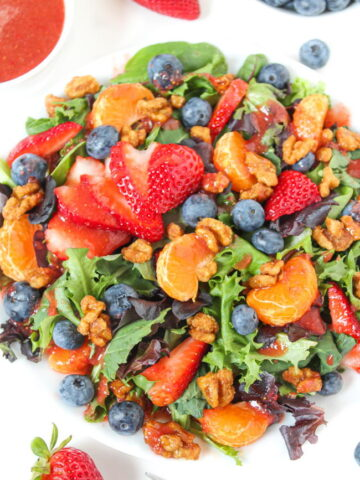 Berry crunch salad on a plate with strawberry dressing