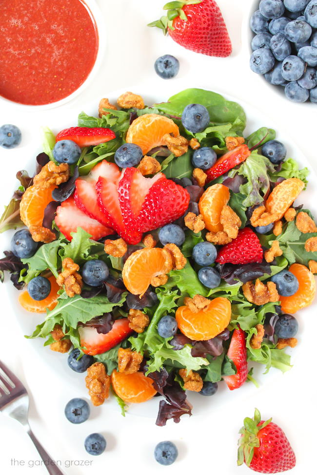 Berry crunch salad on a plate with strawberry dressing on the side