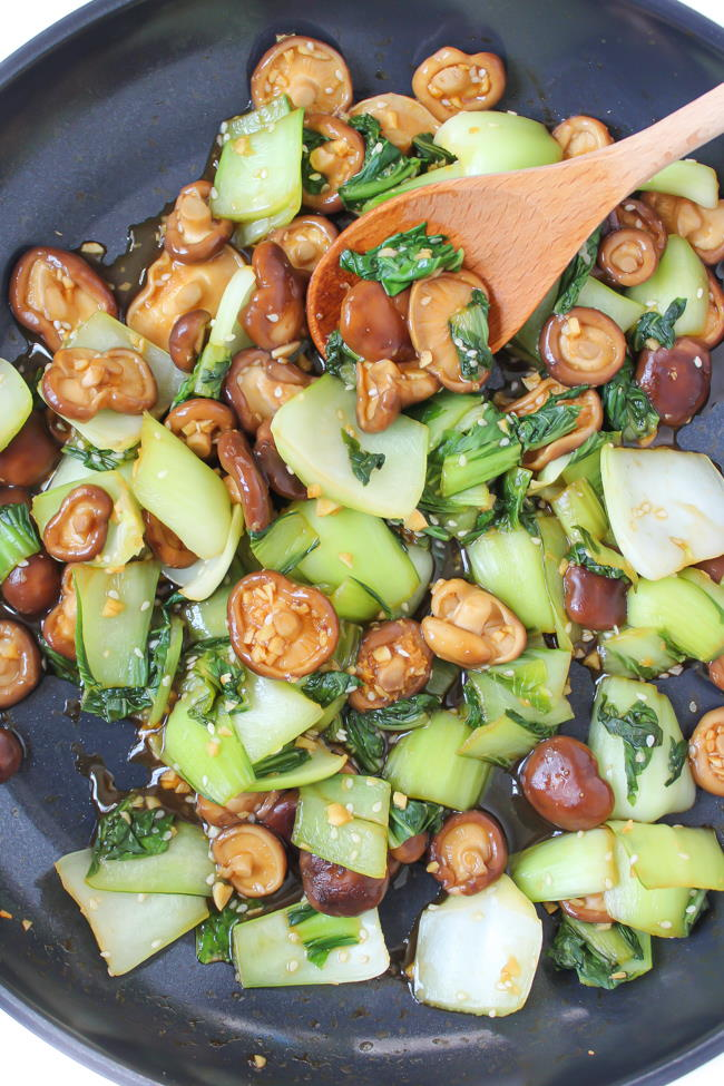Baby boy choy and shiitake mushrooms sautéing in a pan with garlic sauce