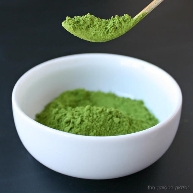 Bowl of organic matcha powder with a bamboo scoop