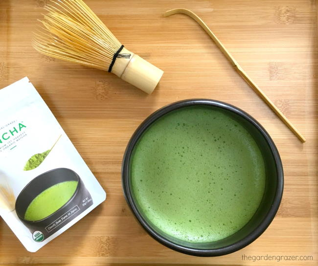 Bowl of whisked matcha sitting on bamboo tray with whisk and scoop