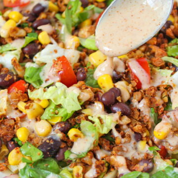Vegan taco salad in a white bowl with dressing on a spoon