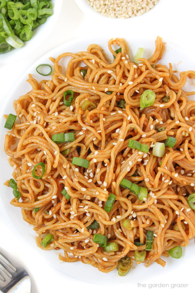 Vegan hoisin peanut butter noodles with sesame seeds on a white plate