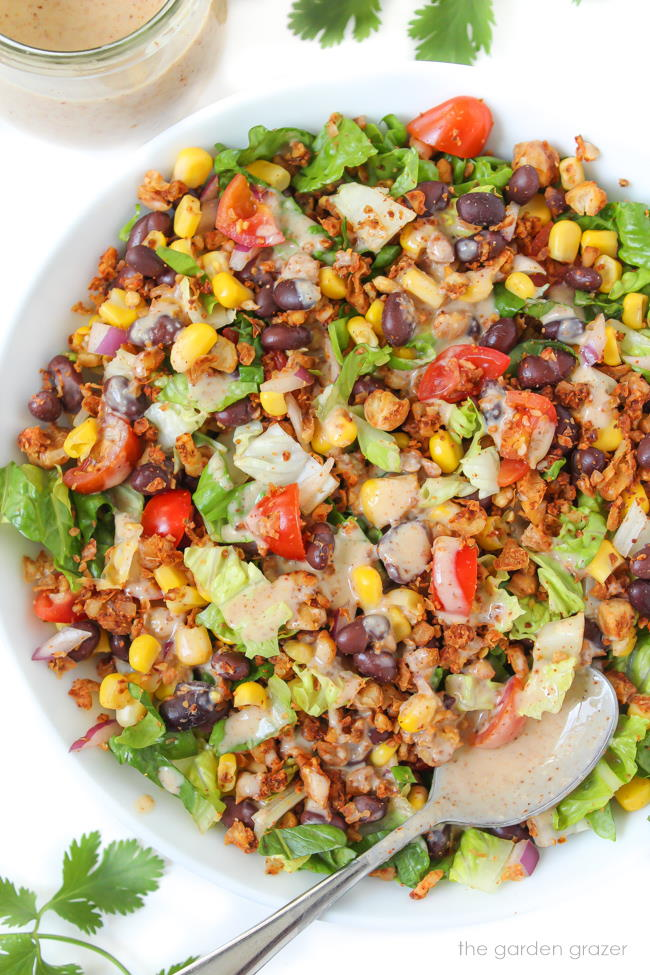 Large white bowl with vegan taco salad and dressing on the side