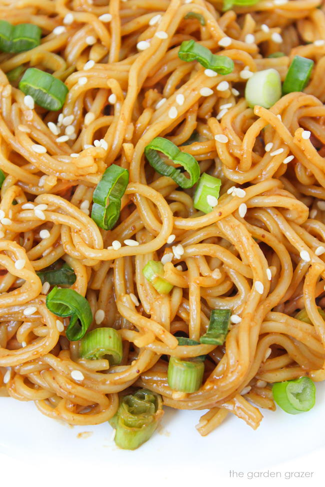 Close-up view of hoisin noodles with green onion and sesame seeds