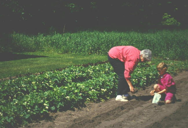 Kaitlin planting seeds in a garden with her grandma