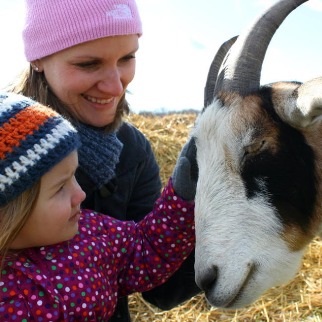 Kaitlin and her daughter petting Michael the goat