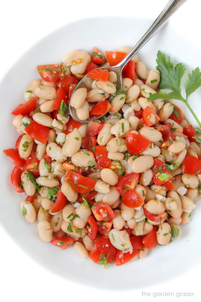 Small bowl of white bean tomato herb salad with spoon