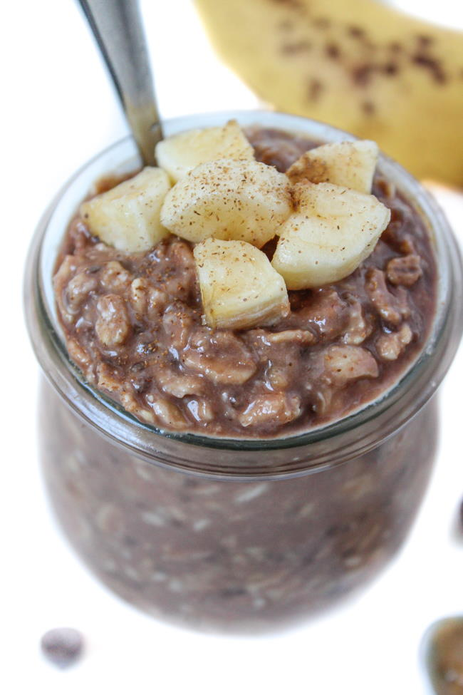 Overnight oats in a small glass jar with banana, peanut butter, and chocolate