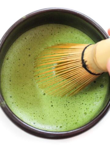 Whisking green tea in a black bowl